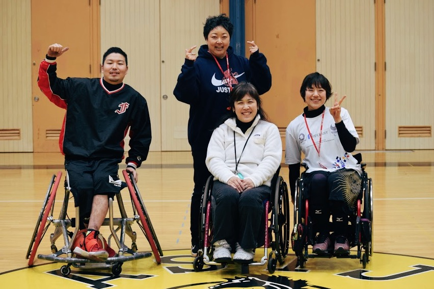 Shinnosuke Moroka, Coach Nagano, Ms. Kyoko Inahara, and Rie Odajima pose after their basketball game with the students.